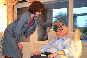 Barbara Watson carrying out an eye test on an elderly gentleman in his own home