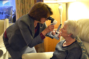 Barbara Watson carrying out an eye test on an elderly lady in their own home