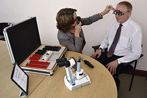 home page image no 3 showing Barbara Watson conducting an eye test in a company office