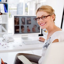 corporate eye care image no 2 office worker wearing reflective spectacles working at a VDU screen