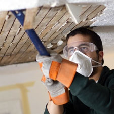 corporate eye care image no 3 joiner ripping out a ceiling wearing safety glasses and mask