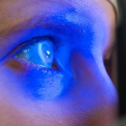 Young corporate lady having an eye test with blue light in her eyes