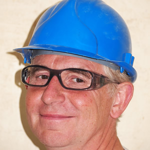image of construction site worker in a hard hat and safety glasses
